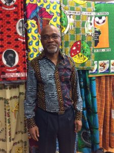 Aliko Songolo in front of a display of African wax cloth